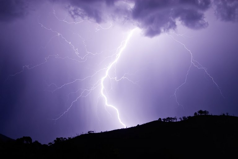 A lightning strike against a light purple sky