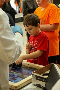 A child screen prints at the WI Science Festival
