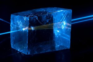 Fluorescence in calcite crystal and birefringence as laser beam splits in two while traveling from left to right