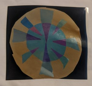 Cellophane layered to create a circle with geometric shapes inside when viewed through polarizers